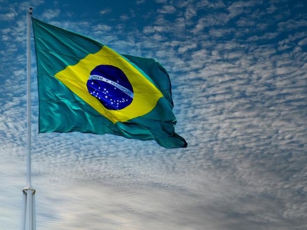 Bandeira do brasil tremulando no céu com nuvens. bandeira brasileira. ordem e progresso.