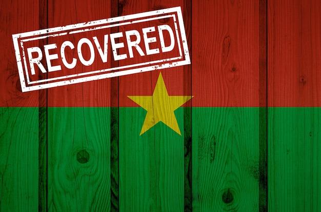 Bandeira do burkina faso que sobreviveu ou se recuperou das infecções da epidemia do vírus corona ou coronavírus. bandeira do grunge com selo recuperado