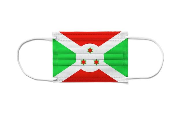 Bandeira do burundi em uma máscara cirúrgica descartável. superfície branca isolada