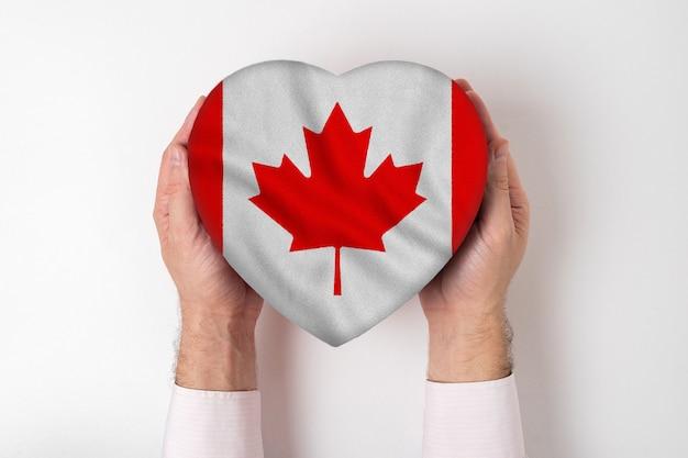 Bandeira do canadá em uma caixa em forma de coração nas mãos masculinas.