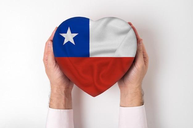 Bandeira do chile em uma caixa em forma de coração nas mãos masculinas.