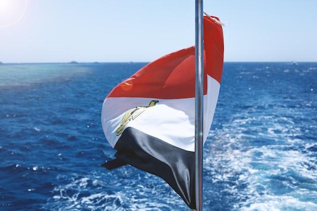 Bandeira do egito acenando vitoriosa com fundo de mar borbulhante e céu azul