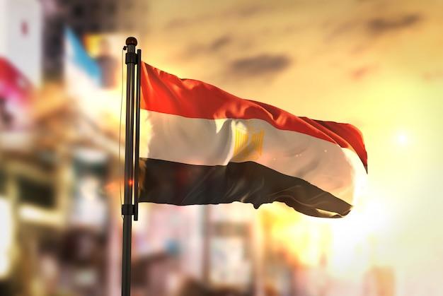 Bandeira do egito contra a cidade fundo borrado no amanhecer luz de fundo