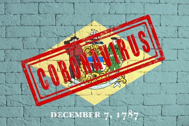 Bandeira do estado de delaware pintada no fundo da parede de tijolo sujo. com carimbo coronavirus, ideia e conceito de saúde, epidemia e doença nos eua