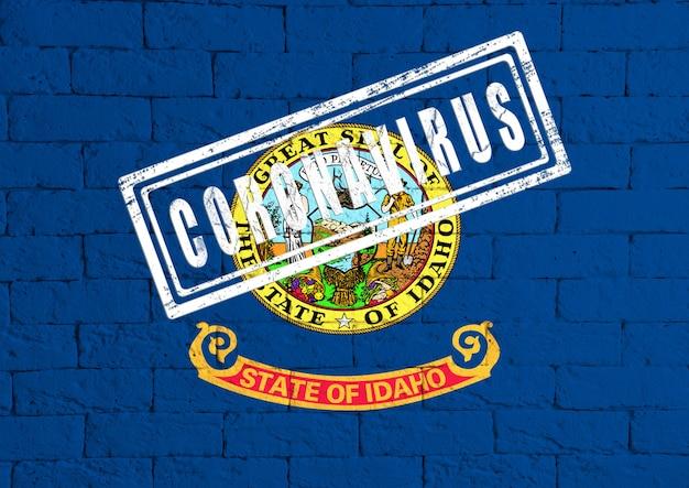 Bandeira do estado de idaho pintada no fundo da parede de tijolo sujo. com carimbo coronavirus, ideia e conceito de saúde, epidemia e doença nos eua