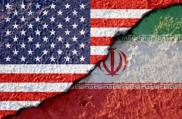 Bandeira do eua e bandeira do irã em danos de parede rachada