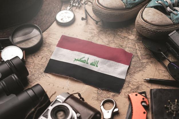 Bandeira do iraque entre acessórios do viajante no mapa antigo do vintage. conceito de destino turístico.