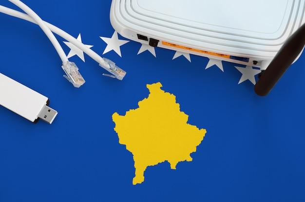 Bandeira do kosovo retratada na tabela com o cabo de internet rj45, adaptador wifi usb sem fio e roteador. conceito de conexão à internet