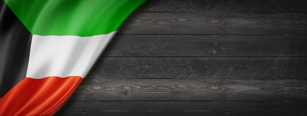 Bandeira do kuwait na parede de madeira preta. banner panorâmico horizontal.