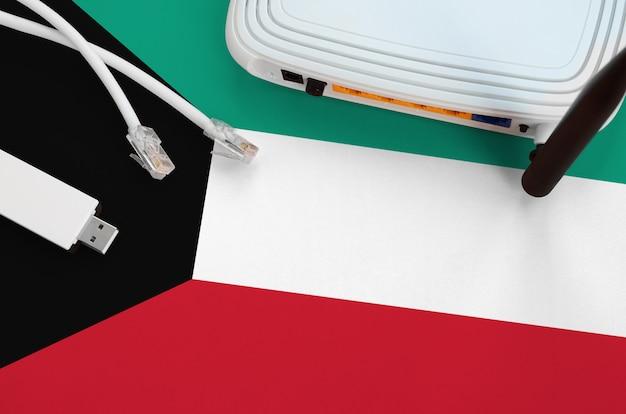 Bandeira do kuwait, retratada na tabela com cabo de internet, adaptador sem fio usb wifi e roteador. conceito de conexão à internet