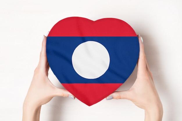 Bandeira do laos em uma caixa em forma de coração nas mãos femininas.