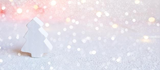 Bandeira do natal - pequena árvore de madeira branca no fundo abstrato das luzes de natal.