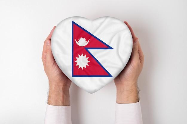 Bandeira do nepal em uma caixa em forma de coração nas mãos masculinas.