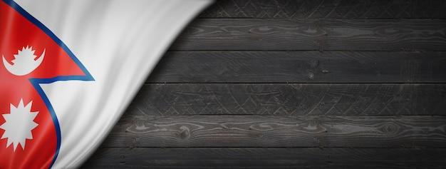 Bandeira do nepal na parede de madeira preta. banner panorâmico horizontal.
