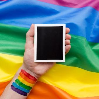 Bandeira do orgulho do arco-íris com mão e foto retrô