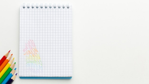 Bandeira do orgulho do arco-íris feita de lápis e espaço de cópia de bloco de notas