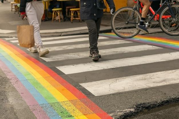 Bandeira do orgulho gay, bandeira do arco-íris da comunidade lgbt na faixa de pedestres com pessoas atravessando em paris. bandeira lgbt como um símbolo dos conceitos de amor, liberdade, igualdade, direitos na vida cotidiana.