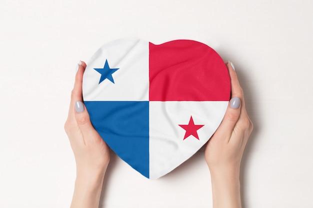 Bandeira do panamá em uma caixa em forma de coração nas mãos femininas.