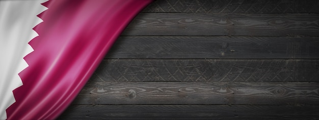 Bandeira do qatar na parede de madeira preta. banner panorâmico horizontal.