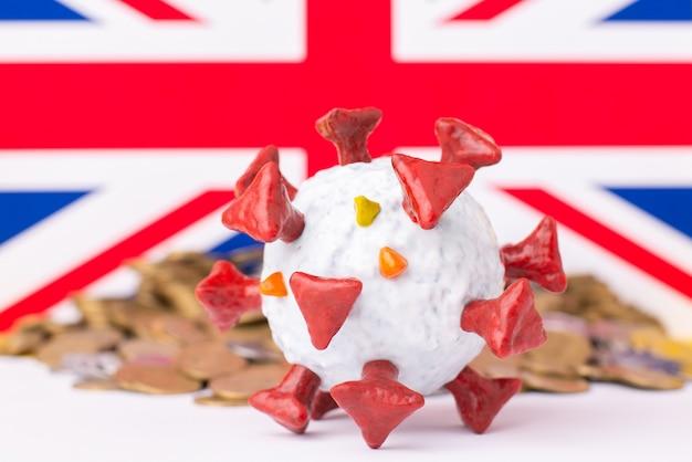 Bandeira do reino unido no modelo feito pelo próprio coronavirus e muitas moedas