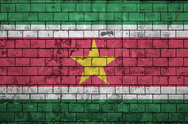 Bandeira do suriname é pintada em uma parede de tijolos antigos
