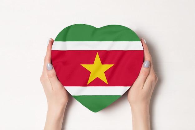 Bandeira do suriname em uma caixa em forma de coração nas mãos femininas.