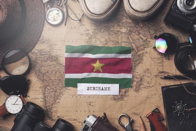 Bandeira do suriname entre acessórios do viajante no mapa antigo do vintage. tiro aéreo
