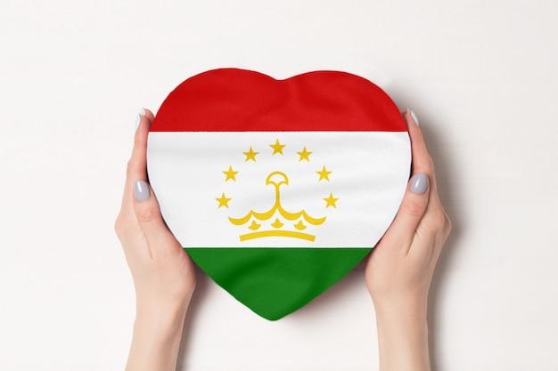 Bandeira do tajiquistão em uma caixa em forma de coração nas mãos femininas.