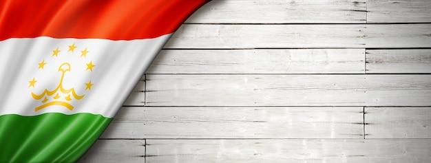 Bandeira do tajiquistão na velha parede branca. banner panorâmico horizontal.