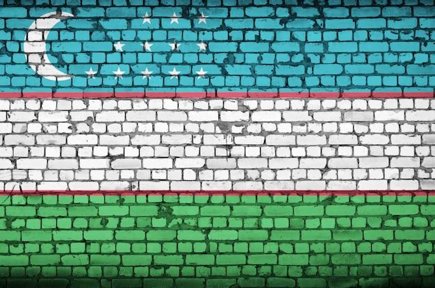 Bandeira do uzbequistão é pintada em uma parede de tijolos antigos