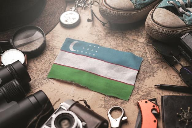 Bandeira do uzbequistão entre acessórios do viajante no antigo mapa vintage. conceito de destino turístico.