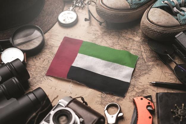 Bandeira dos emirados árabes unidos entre acessórios do viajante no antigo mapa vintage. conceito de destino turístico.
