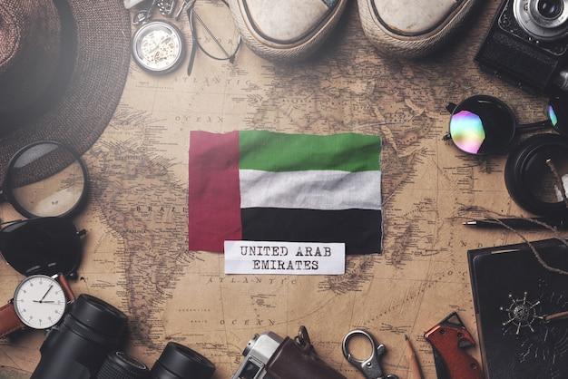 Bandeira dos emirados árabes unidos entre acessórios do viajante no antigo mapa vintage. tiro aéreo