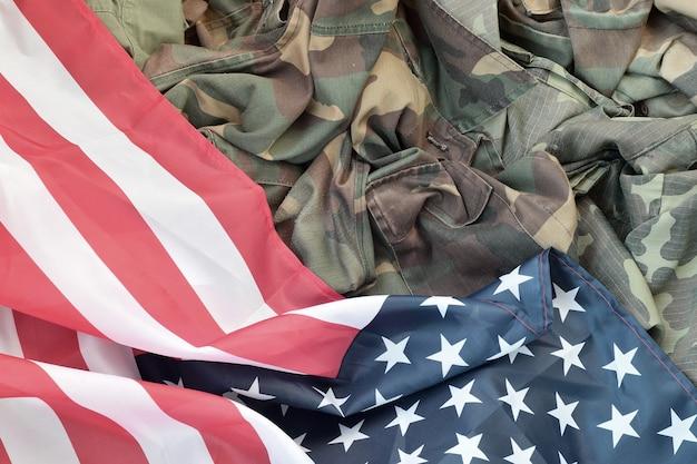 Bandeira dos estados unidos da américa e jaqueta de uniforme militar dobrada. símbolos militares
