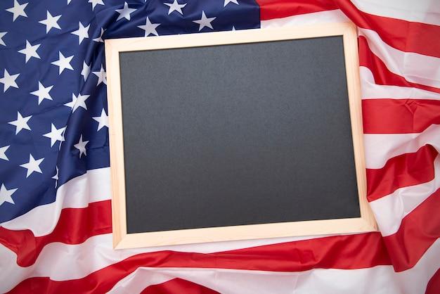 Bandeira dos eua de tecido e quadro preto ou lousa na parte superior com espaço para texto, vista superior