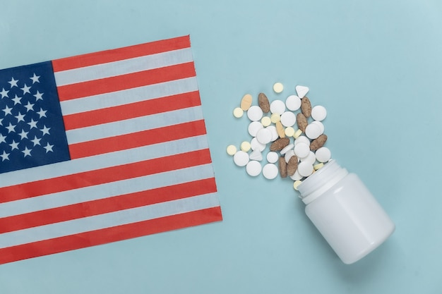 Bandeira dos eua e frasco de comprimidos em um azul Foto Premium