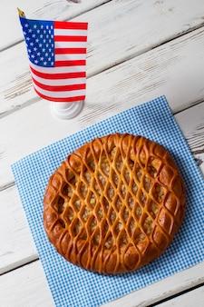 Bandeira dos eua e torta redonda. torta no guardanapo ao lado da bandeira. pastelaria fresca na mesa branca. torta tradicional com recheio de frutas.