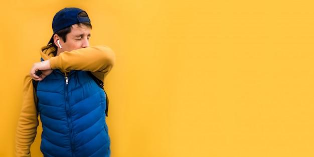 Bandeira europeia 6x3 homem europeu com roupas azuis espirra no cotovelo pelo vírus, fechando os olhos. o conceito de espirrar em um copyspace amarelo do fundo.