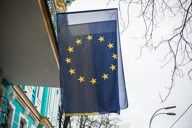 Bandeira europeia e bandeira da ucrânia ao vento do lado de fora do prédio