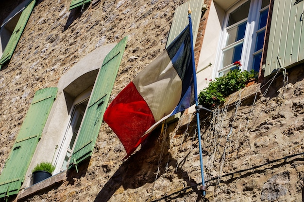 Bandeira francesa pregada na fachada de uma antiga casa de pedra. villefranche de conflent na frança