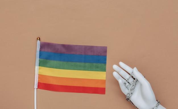 Bandeira lgbt e mão manequim enrolada em corrente de aço em fundo marrom