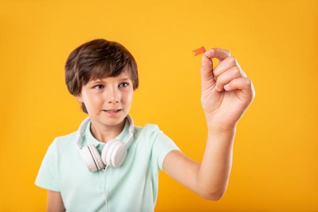 Bandeira minúscula. estudante inteligente e charmoso usando fones de ouvido e segurando um alfinete Foto Premium