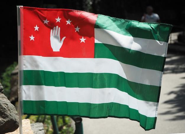Bandeira nacional da abkházia com listras brancas e verdes e mão aberta