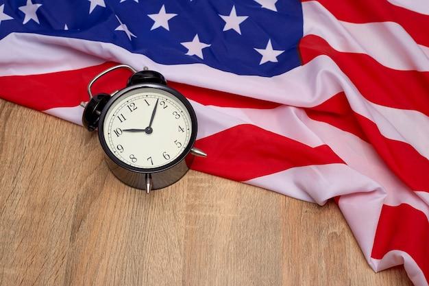 Bandeira nacional da américa e preto despertador no antigo fundo de madeira