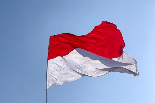 Bandeira nacional da indonésia e mônaco com fundo branco do céu nublado.