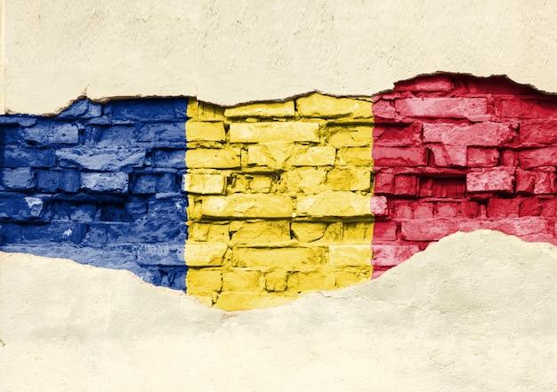 Bandeira nacional da romênia em um fundo de tijolo. parede de tijolos com gesso, fundo ou textura parcialmente destruída.