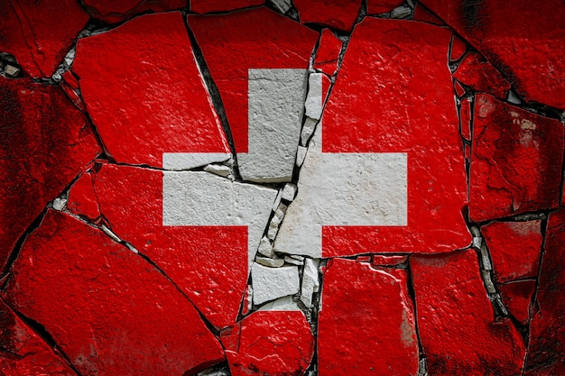 Bandeira nacional da suíça retratando em cores de tinta em um velho muro de pedra. bandeira da bandeira no fundo da parede quebrada.
