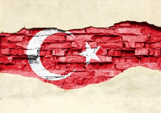 Bandeira nacional da turquia em um fundo de tijolo. parede de tijolos com gesso, fundo ou textura parcialmente destruída.