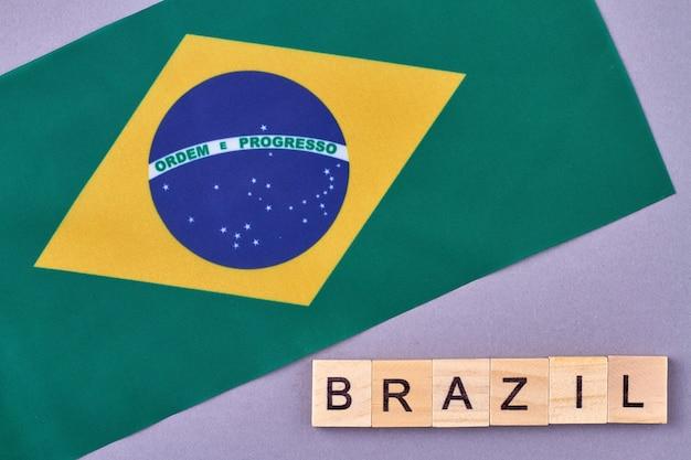 Bandeira nacional do brasil. blocos do alfabeto de madeira com letras isoladas em fundo violeta.