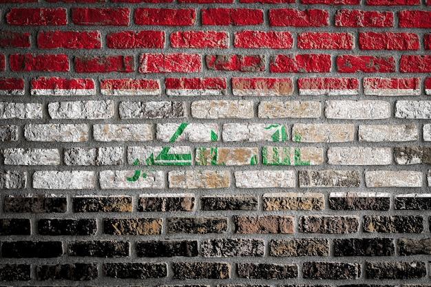 Bandeira nacional do iraque em uma velha parede de tijolos